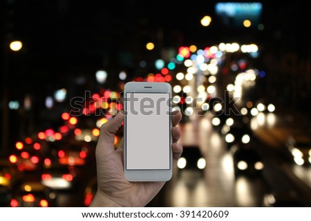 Man hand holding empty screen of smart phone and blurred traffic jam at night background. - stock photo