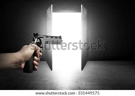 Man hand holding gun and aim to the door - stock photo
