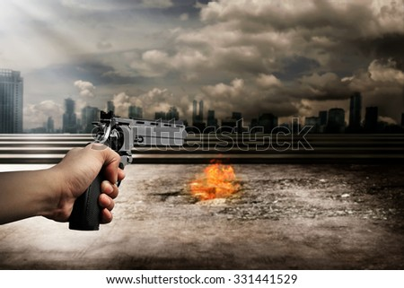 Man hand holding gun and aiming to the burn city - stock photo