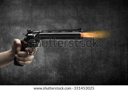 Man hand holding gun and firing it - stock photo