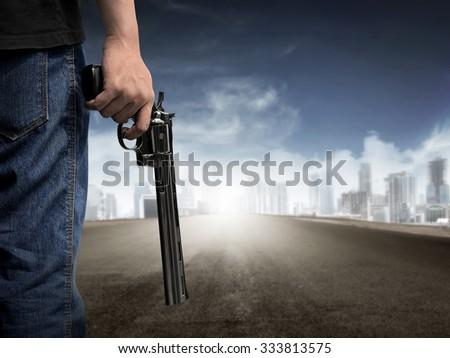 Man hand holding gun on empty highway - stock photo