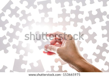Man hand holding jigsaw puzzle piece - stock photo