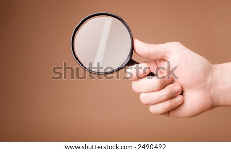 Man hand holding magnifying glass on the beige background