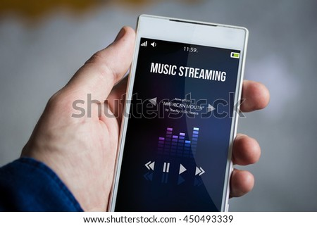 man hand holding music streaming smartphone. All screen graphics are made up.