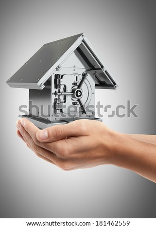 Man hand holding object ( Bank Safe in form houses ) High resolution  - stock photo