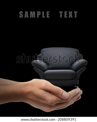 Man hand holding object ( modern leather chair ) isolated on black background. High resolution  - stock photo