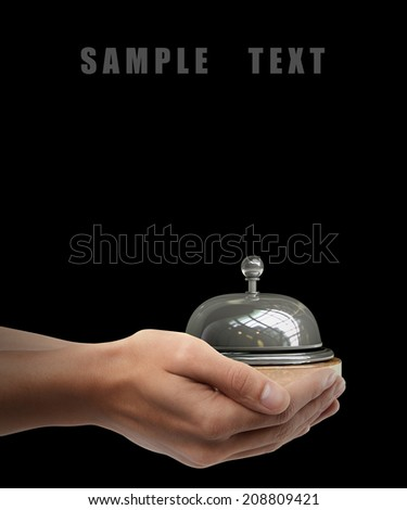 Man hand holding object ( Reception bell ) isolated on black background. High resolution  - stock photo