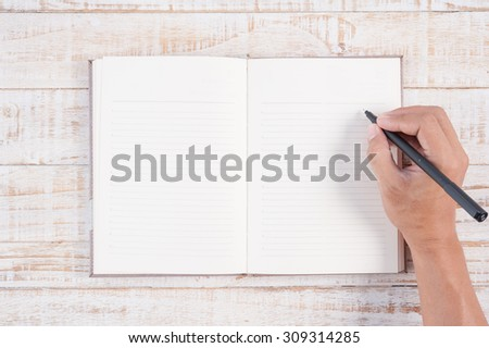 Man hand holding pen and writing notebook  on wood table for text and background.copy space - stock photo