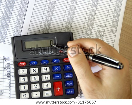 man hand holding pen on calculator buttons in office - stock photo