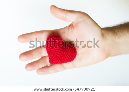 Man hand holding red crocheted heart. Valentine's Day. Symbol of love.