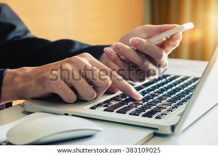 man hand holding smart phone and typing with laptop in morning light.vintage effect