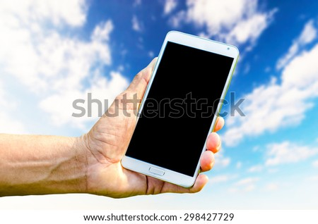 Man hand holding smartphone against on blue sky background soft focus. - stock photo