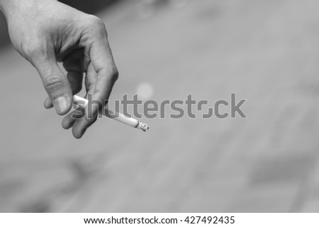 man hand holding smoking a cigarette with smoke cigarette in black and white / monotone image - stock photo