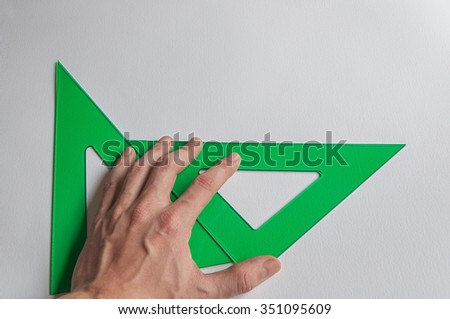 Man hand holding technical drawing set square on white textured paper.