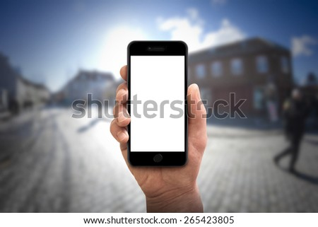 Man hand holding the smartphone isolated on blured city background  - stock photo