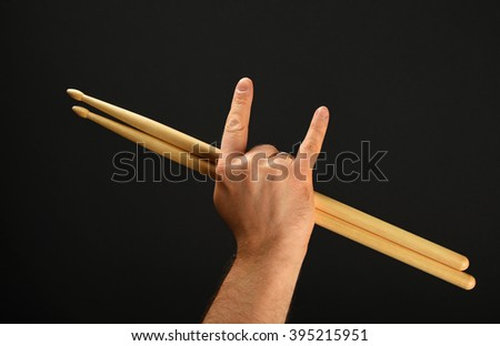 Man hand holding two drumsticks with devil horns rock metal gesture sign over black background, back view - stock photo