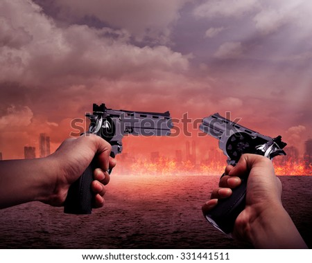 Man hand holding two gun and aiming to the burn city - stock photo