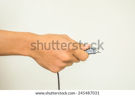 Man hand holding usb cable - stock photo