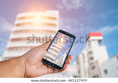 Man hand holding white smartphone with cityscape screen on Blurred city bokeh background