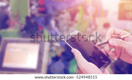 man hand holding writing on electronic screen device software with automated wireless robot arm in factory background - industrial concept