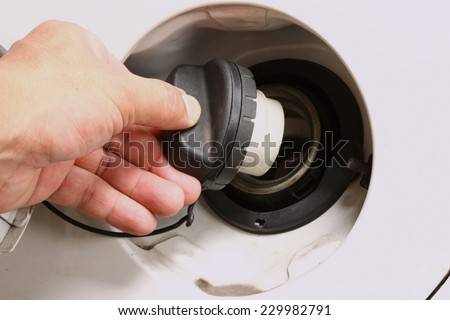 Man hand in action of open car fuel tank lid black color in the scene focus at the car fuel tank lid.     - stock photo
