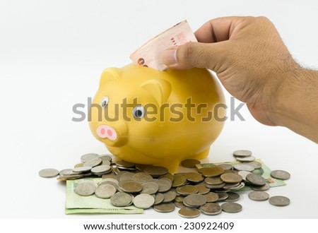 man hand inserting a coin into a piggy bank