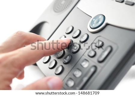man hand is dialing a phone number with picked up headset - stock photo