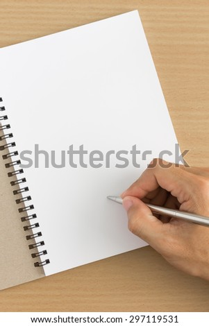 man hand is writing on blank notebook. Focus on finger - stock photo