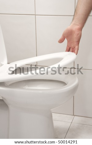 Man hand lifting up a toilet seat - stock photo