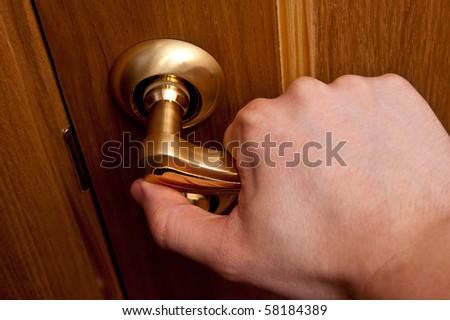 Man hand opening wooden door. Horizontal shot - stock photo