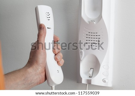 Man hand picking up the entry phone - stock photo