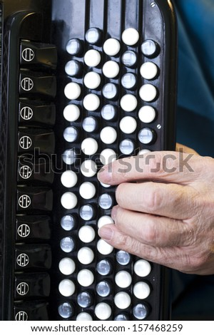 man hand playing traditional harmonica, vertical shot - stock photo