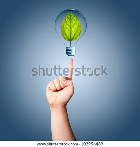 Man hand pointing to light bulb with green plant inside. Concept for idea for environmental conservation - stock photo
