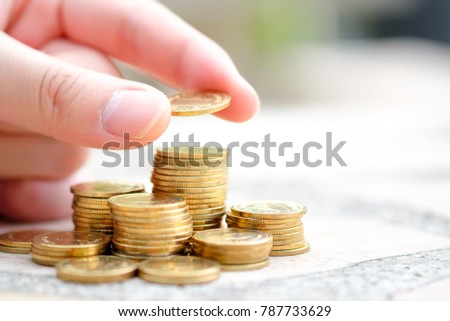 Man hand putting coin on stack of coins. Concept of saving money.