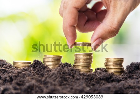 man hand putting coins into growth of golden coins in soil with green leaf background - stock photo