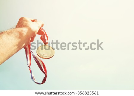 man hand raised, holding gold medal against Sky. award and victory concept. selective focus. retro style image.  - stock photo