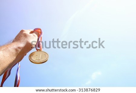 man hand raised, holding gold medal against skyl. award and victory concept. selective focus. retro style image. - stock photo