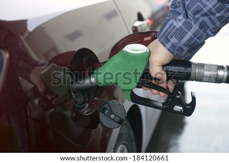 man hand refilling up gas tank of the car with green eco fuel on a filling station