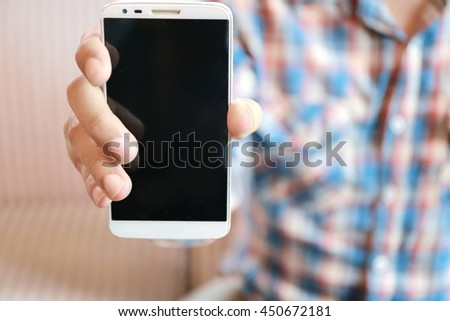 Man hand show his smart phone, Happy trendy young man showing blank screen of his mobile,  copy space on phone screen for add text.