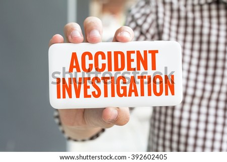 Man hand showing ACCIDENT INVESTIGATION word phone with  blur business man wearing plaid shirt. - stock photo