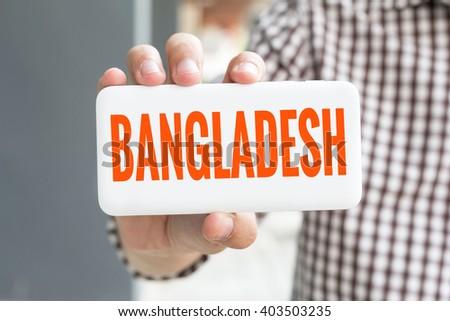 Man hand showing BANGLADESH word phone with  blur business man wearing plaid shirt. - stock photo