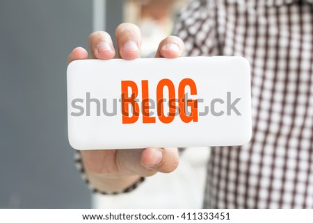 Man hand showing BLOG word phone with  blur business man wearing plaid shirt. - stock photo