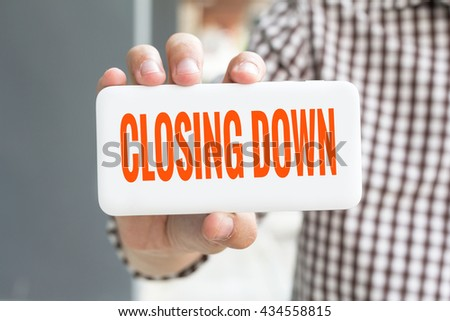 Man hand showing CLOSING DOWN word phone with  blur business man wearing plaid shirt. - stock photo