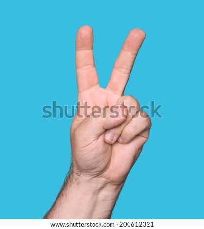 Man hand showing the sign of victory and peace isolated on blue background  - stock photo