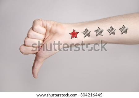 Man hand showing thumbs down and one star rating on the arm skin. Dislike - stock photo