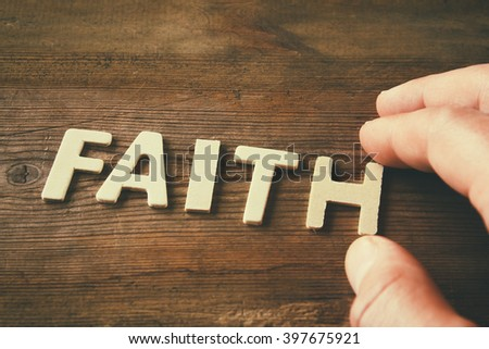 man hand spelling the word FAITH from wooden letters, retro style image  - stock photo