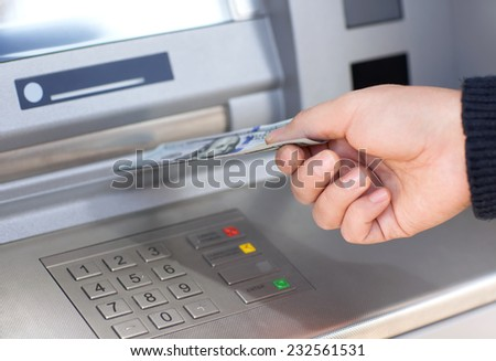 man hand taking money from an ATM - stock photo