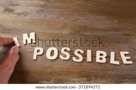 man hand taking of the letters im from the word imposible so it says possible - stock photo