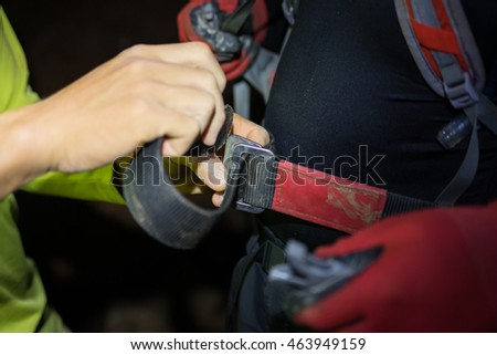 Man hand tightening rock climbing equipments with rope, hook, belt in dark cave in Son Dong, the largest cave in the world