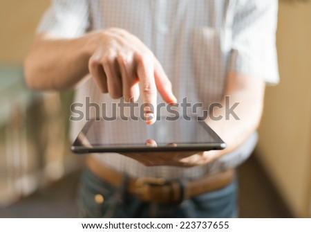 Man hand touching screen on modern digital tablet pc - stock photo